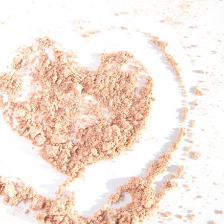 Heart symbol drawn on the scattered powder on a white background.
